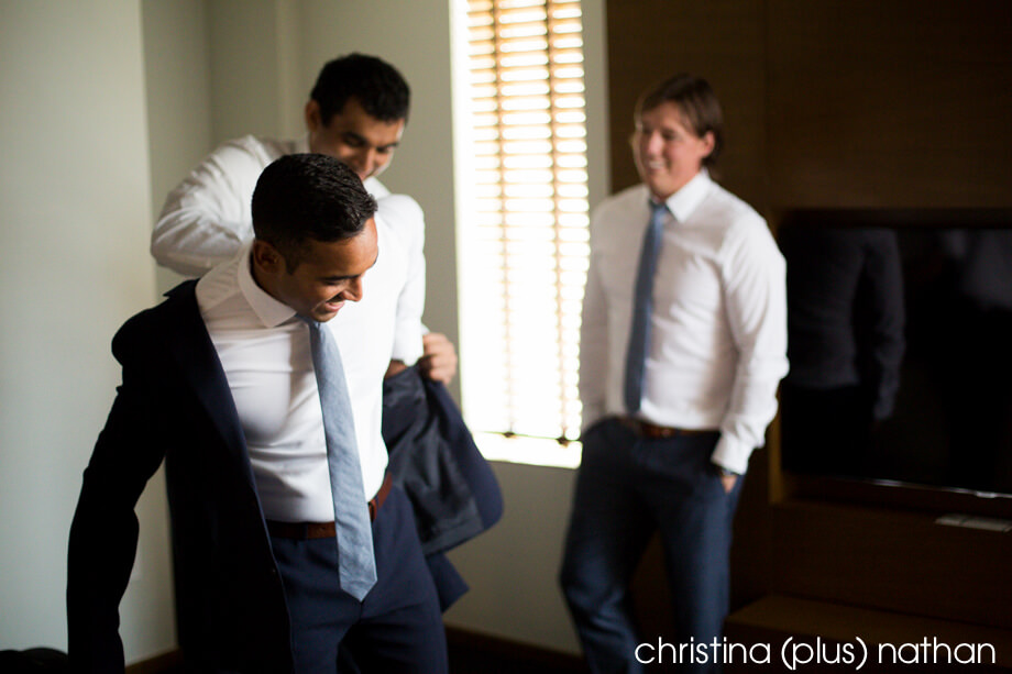 Groomsmen helping groom dress for his wedding photos in Calgary