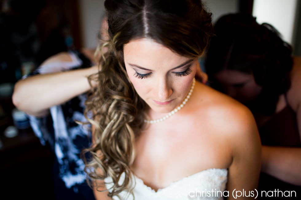 Bride putting on pearl necklace before her wedding ceremony photographed by christina (plus) nathan