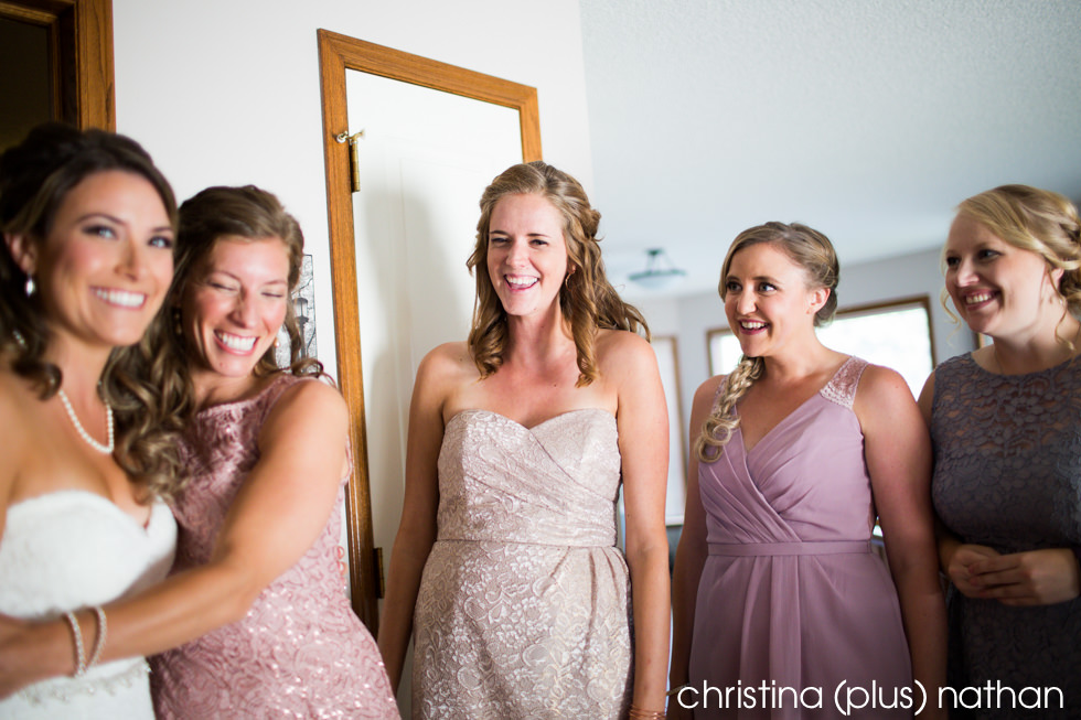 Bridesmaids laughing with the bride before her wedding ceremony