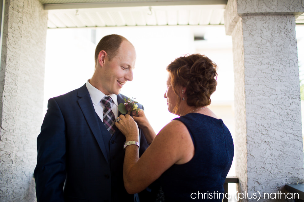 Mother pins boutonnière on her son, the groom before his Calgary wedding