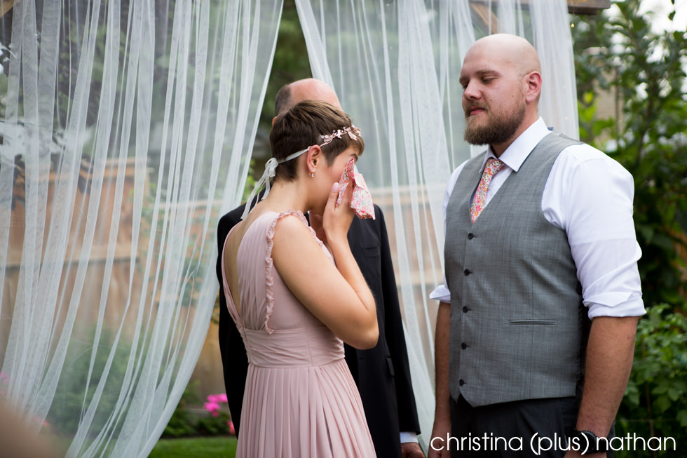 Bride cries at Calgary backyard wedding ceremony photographed by Calgary wedding photographers christina (plus) nathan