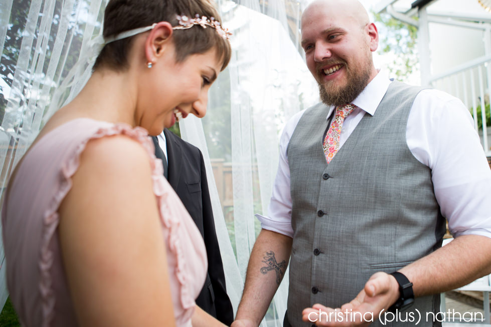 Bride and groom exchange rings in a backyard wedding ceremony