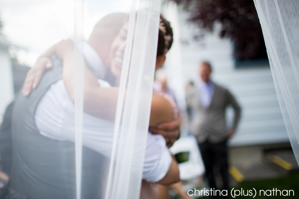Artistic photograph of bride and groom hugging after wedding ceremony