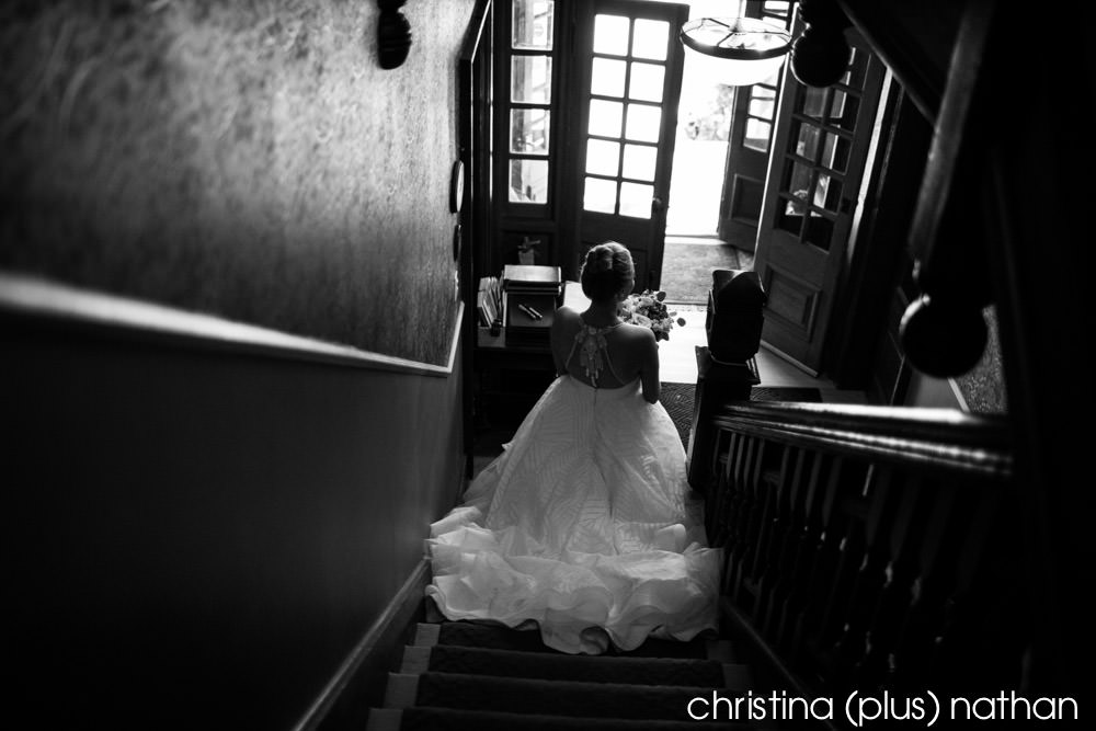 Bride comes down the stairs before she walks down the aisle at her Bow Valley Ranche wedding