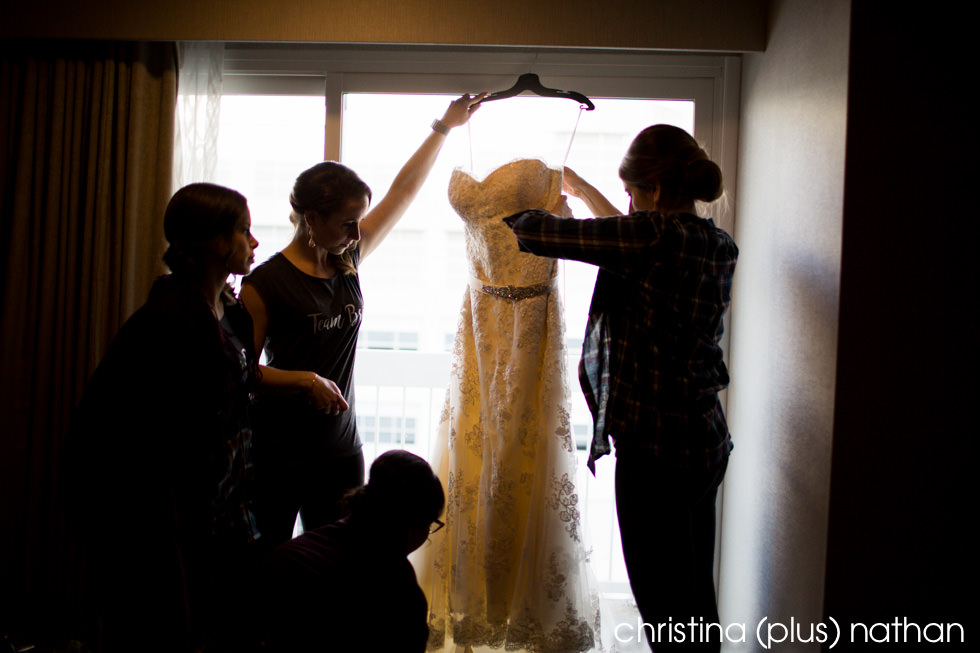 Photography of bridal party getting wedding dress ready for bride