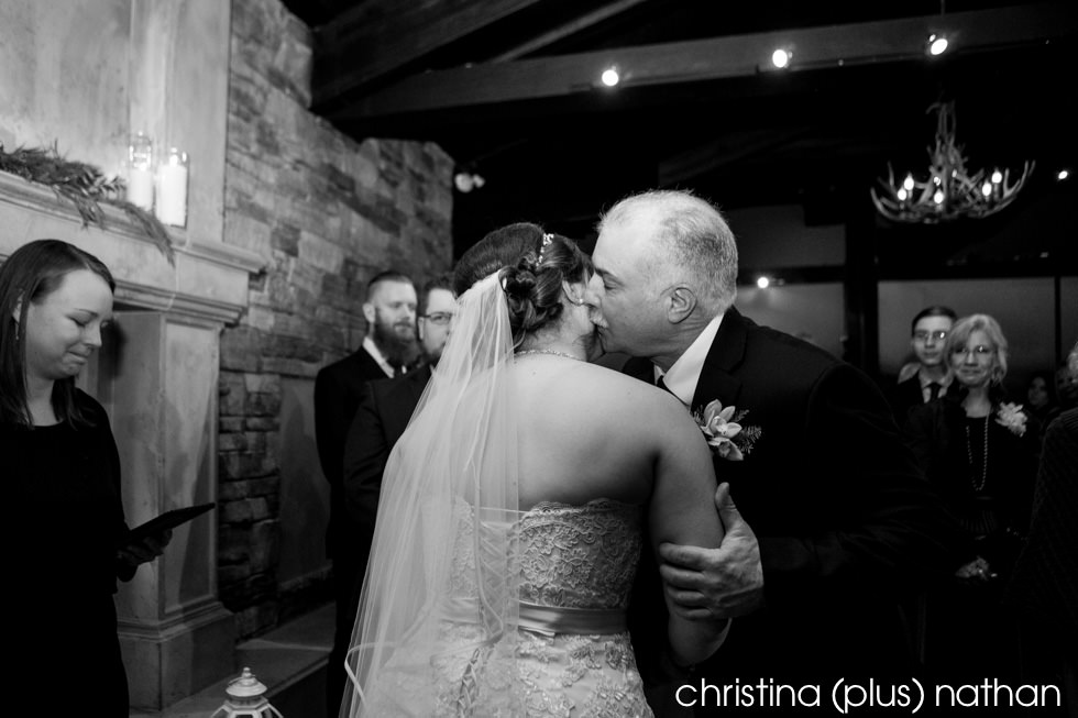 Dad kissing bride at wedding ceremony Lake House Calgary