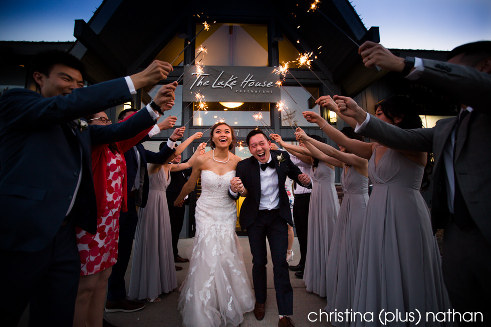 Bride and groom walk under sparklers at The Lake House restaurant in Calgary, AB