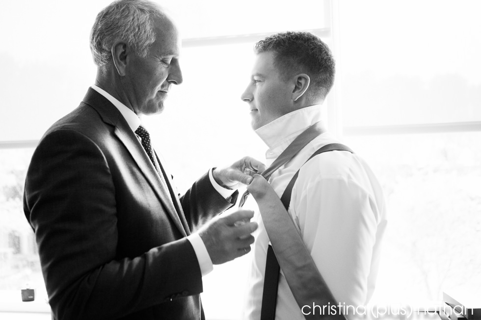 Father of the groom helps his son with his tie before his Sheraton Eau Claire wedding