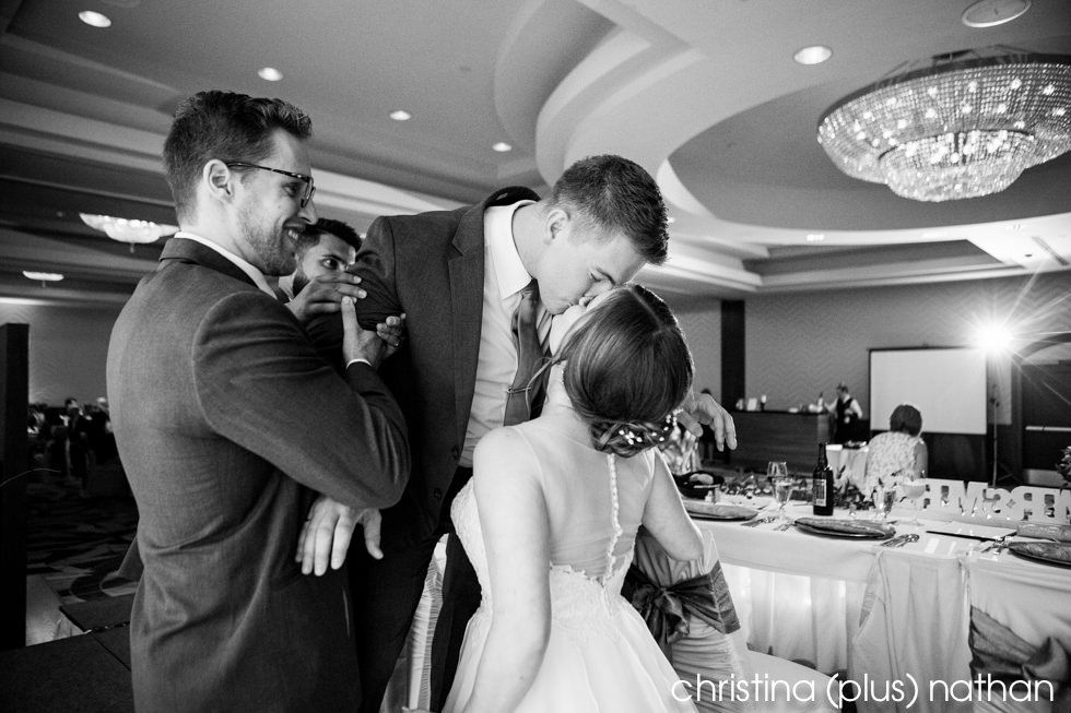 Newlyweds share a kiss at their Calgary Sheraton Eau Claire wedding reception photographed by Calgary wedding photographers christina (plus) nathan
