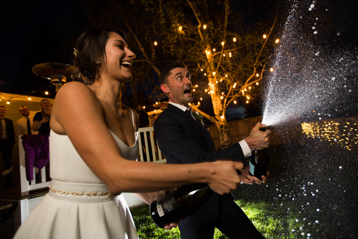 popping champagne bride and groom backyard wedding